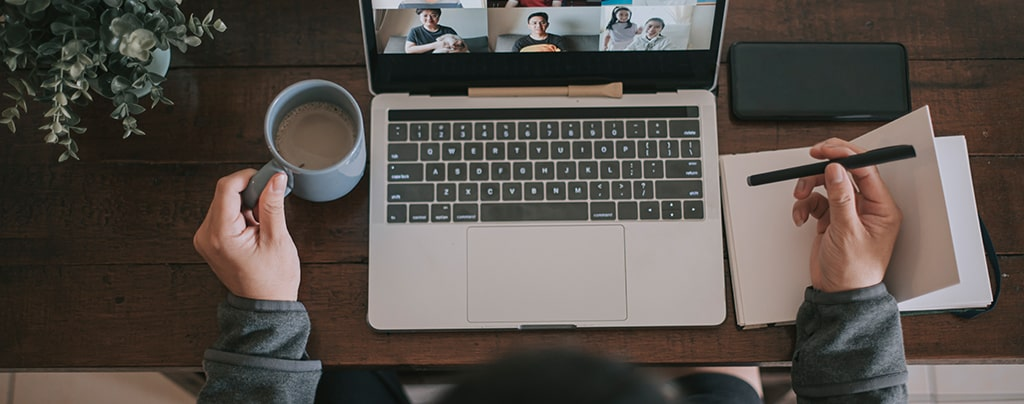 remote worker sitting at desk with laptop on a conference call